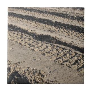 Tire tracks in dirt tile