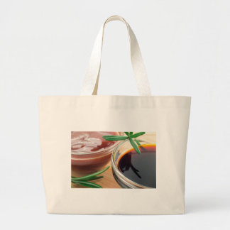 Tomato ketchup and soy sauce in a transparent bowl large tote bag