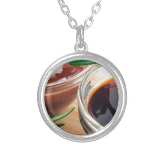 Tomato ketchup and soy sauce in a transparent bowl silver plated necklace