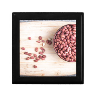 Top view of a brown bowl with raw peanuts gift box