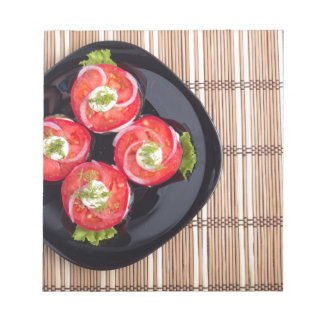 Top view of a dish with fresh sliced tomatoes notepad
