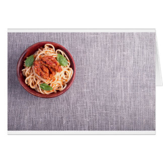 Top view of a gray mat with a spaghetti card