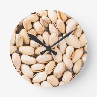Top view of a lot of salty pistachios round clock