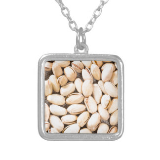 Top view of a lot of salty pistachios silver plated necklace
