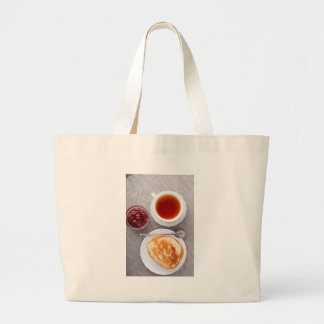Top view of a plate of hot pancakes with vintage large tote bag
