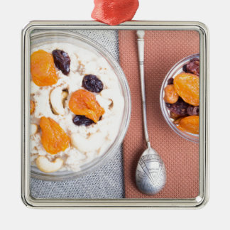 Top view of a portion of oatmeal with fruit Silver-Colored square decoration