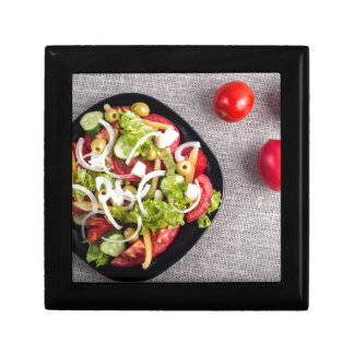Top view of a small bowl of vegetables salad small square gift box