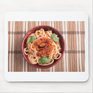 Top view of a thin spaghetti in a brown small wood mouse pad