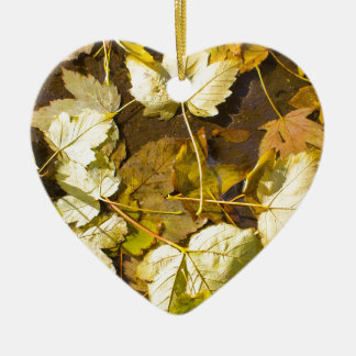 Top view of a wet autumn leaves ceramic heart decoration