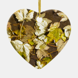 Top view of a wet autumn maple leaves ceramic heart decoration