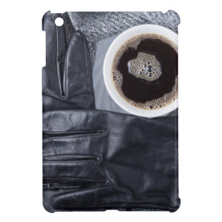 Top view of a white cup of coffee and black gloves case for the iPad mini