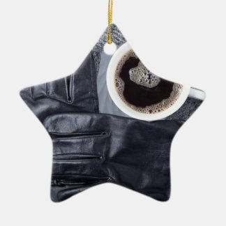 Top view of a white cup of coffee and black gloves ceramic ornament