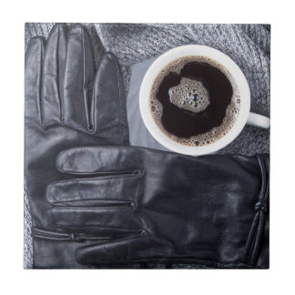 Top view of a white cup of coffee and black gloves ceramic tile