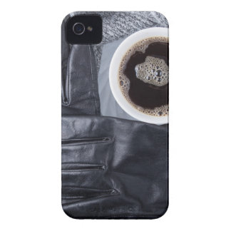 Top view of a white cup of coffee and black gloves iPhone 4 cover