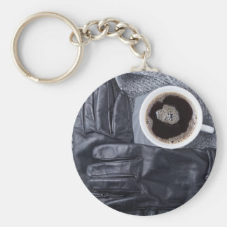Top view of a white cup of coffee and black gloves key ring