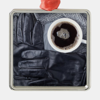 Top view of a white cup of coffee and black gloves metal ornament