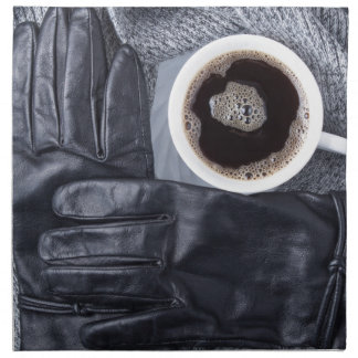 Top view of a white cup of coffee and black gloves napkin