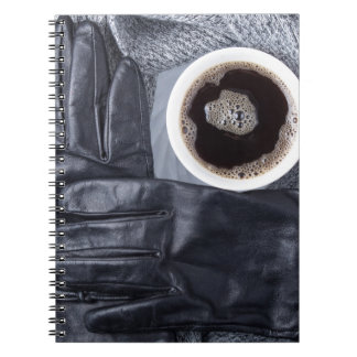Top view of a white cup of coffee and black gloves notebooks