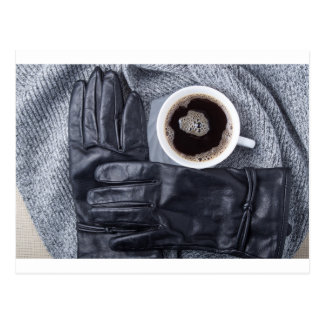 Top view of a white cup of coffee and black gloves postcard