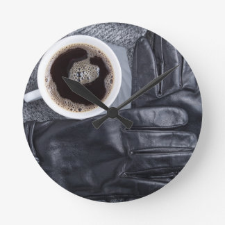 Top view of a white cup of coffee and black gloves round clock