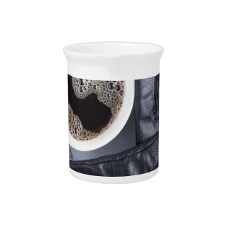 Top view of a white cup of coffee and gray woolen pitcher