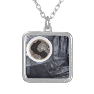 Top view of a white cup of coffee and gray woolen silver plated necklace