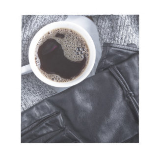 Top view of a white cup with coffee notepad