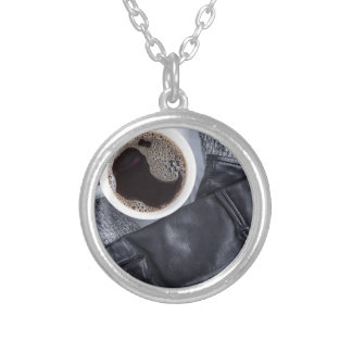 Top view of a white cup with coffee silver plated necklace
