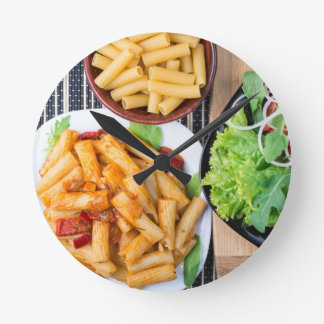 Top view of cooked rigatoni pasta with vegetables round clock
