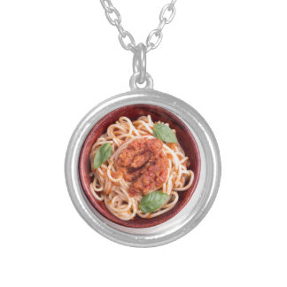 Top view of cooked spaghetti with tomato relish silver plated necklace