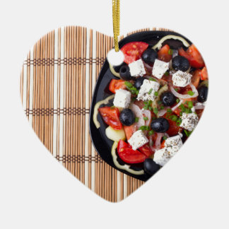 Top view of fresh vegetarian salad on a black ceramic heart decoration