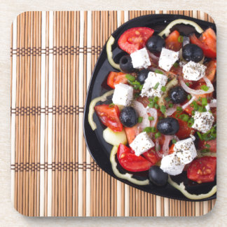 Top view of fresh vegetarian salad on a black coaster