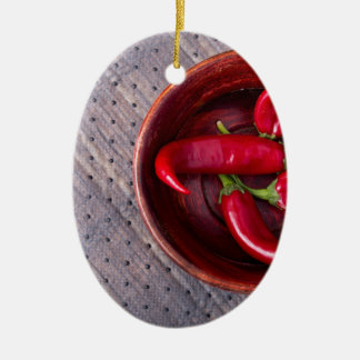 Top view of hot red chili peppers in a brown wood ceramic ornament