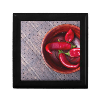 Top view of hot red chili peppers in a brown wood gift box