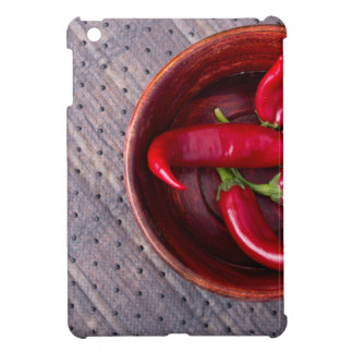 Top view of hot red chili peppers in a brown wood iPad mini covers