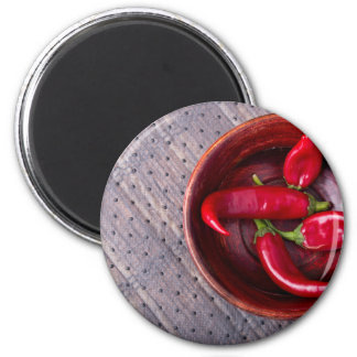 Top view of hot red chili peppers in a brown wood magnet