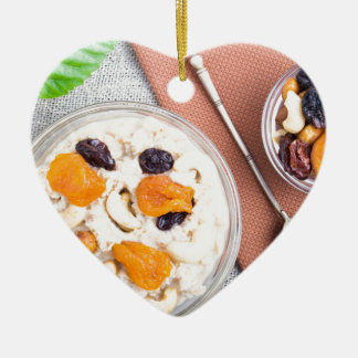 Top view of oatmeal porridge with raisins, cashews ceramic heart decoration