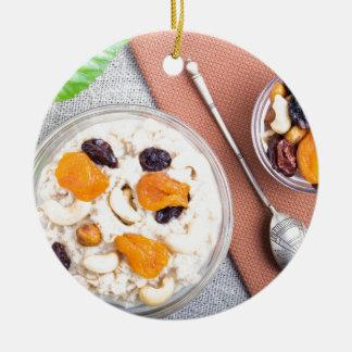 Top view of oatmeal porridge with raisins, cashews round ceramic decoration