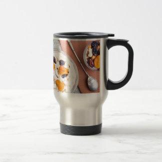 Top view of oatmeal porridge with raisins, cashews travel mug