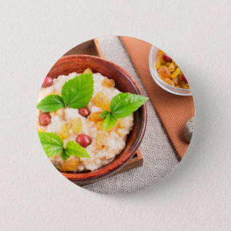 Top view of oatmeal with raisins, berries and herb 6 cm round badge