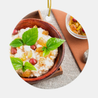 Top view of oatmeal with raisins, berries and herb ceramic ornament