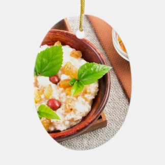 Top view of oatmeal with raisins, berries and herb ceramic oval decoration