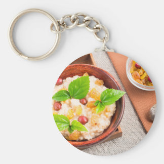 Top view of oatmeal with raisins, berries and herb key ring