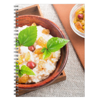Top view of oatmeal with raisins, berries and herb notebook