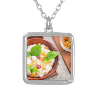 Top view of oatmeal with raisins, berries and herb silver plated necklace