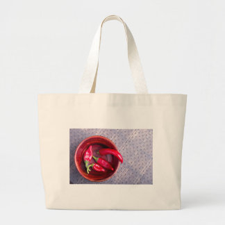 Top view of the fruits of of hot red chili peppers large tote bag