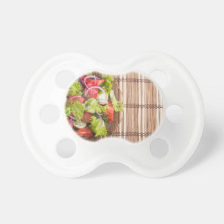 Top view of vegetarian salad from fresh vegetables baby pacifier