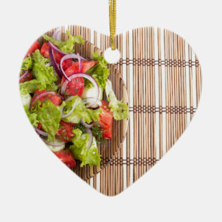 Top view of vegetarian salad from fresh vegetables ceramic heart decoration