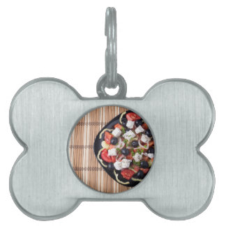 Top view of vegetarian salad in a black plate pet tag