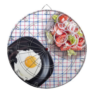 Top view on a black plate with a fried egg dart boards